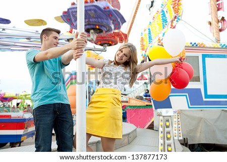 Young couple of teenagers visiting a fun fair ground with rides and lights around them, holding balloons, being playful and joyful during a sunny day. - stock photo