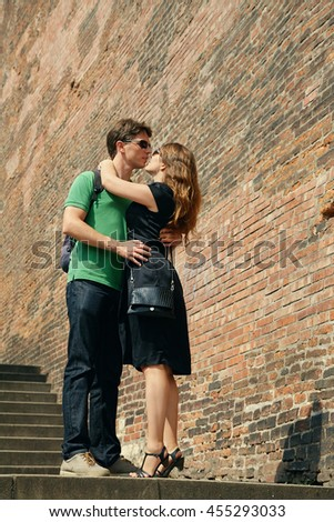 young couple of travelers walking on a street of European city and sightseeing - stock photo