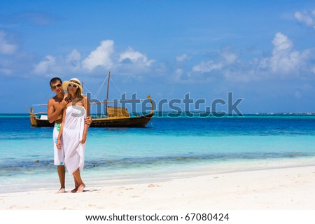 Young couple on a beach on a background a yacht - stock photo
