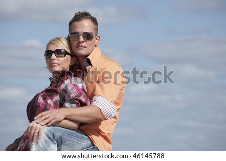 Young couple on a blue sky background - stock photo