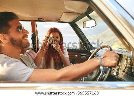 Young couple on a road trip. man driving car with woman taking pictures with retro camera. - stock photo