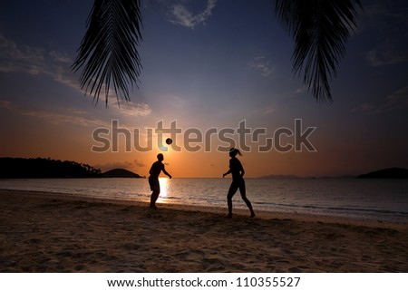 Young couple on a summer beach vacation playing with a beachball - stock photo