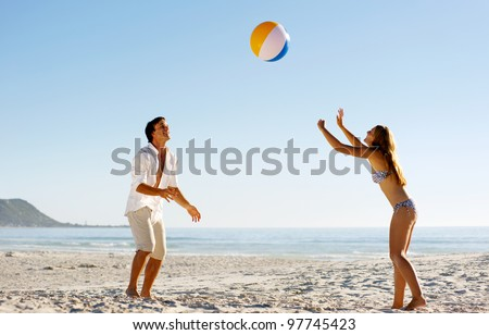 Young couple on a summer beach vacation playing with a beachball and having carefree fun - stock photo