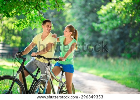 Young couple on bicycles in the park - stock photo