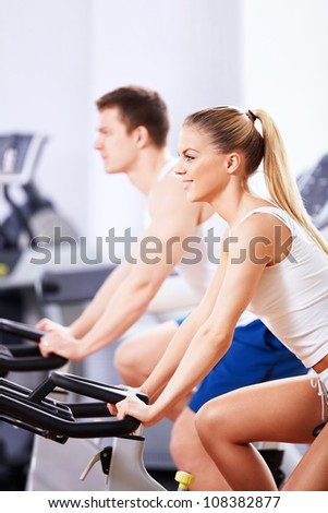 Young couple on bikes indoors - stock photo