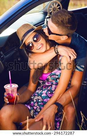 Young couple on road trip. Young couple sitting on the hood of their car with man answering a phone call and woman sitting by. Car is parked alongside coastal seashore with bright sunlight. sunshine - stock photo