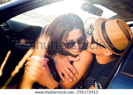 Young couple on road trip.Young couple sitting on the hood of their car with man answering a phone call and woman sitting by.Car is parked alongside coastal seashore with bright sunlight.sunset,bright - stock photo