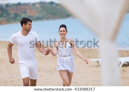 Young couple on sand seashore in cloudy day. Attractive couple in white running holding hands along sand beach - stock photo