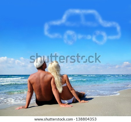 young couple on sea sand beach dreaming about the own car concept - stock photo