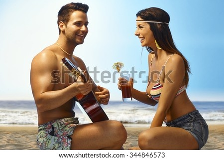 Young couple on the beach. Man playing guitar, woman drinking cocktail, enjoying time together. - stock photo