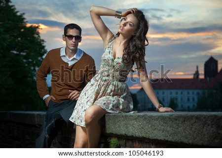 Young couple on the sunset background - stock photo