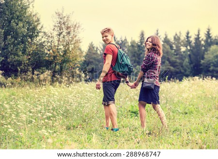 Young couple on the walk in summer forest - stock photo