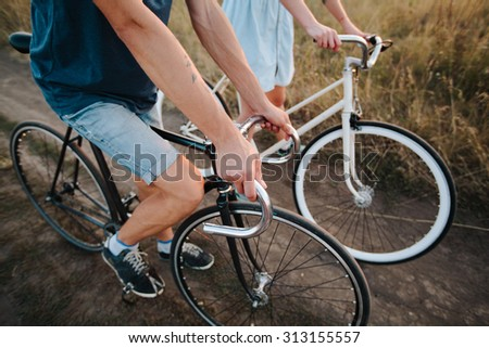 young couple on vintage bikes riding - stock photo