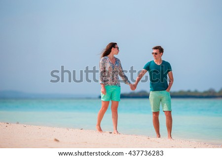 Young couple on white beach during summer vacation. Happy lovers enjoy their honeymoon at exotic island - stock photo