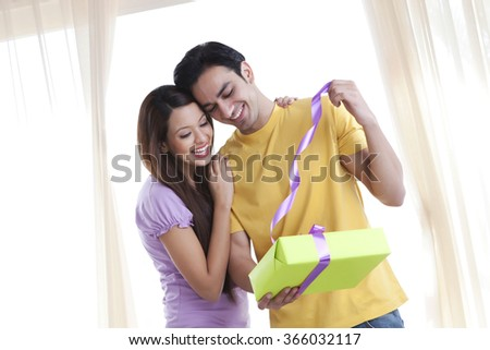 Young couple opening a gift - stock photo