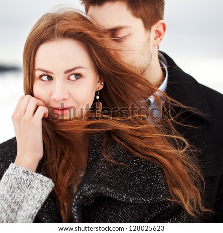 Young couple outdoor sensual portrait in cold windy weather in the field cowered with snow - stock photo