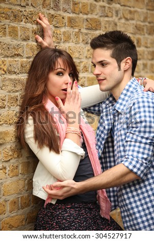 young couple outdoors in inconvenient situation - stock photo
