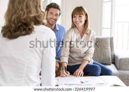 Young couple owners meeting real estate agent for house investment. Signing a contract - stock photo
