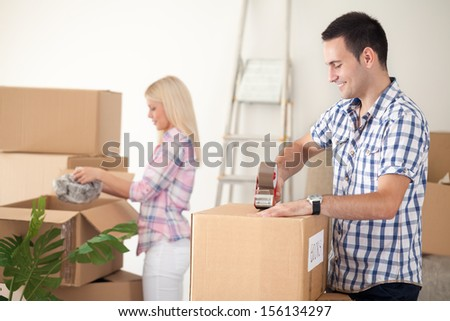 young couple packing moving boxes, ready for move out - stock photo