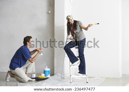 Young Couple Painting Room - stock photo
