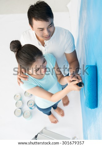 Young couple painting wall at home, view from above - stock photo