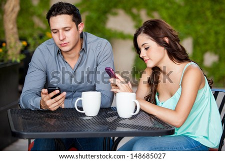 Young couple passing the time by using their cell phones on a bad date - stock photo