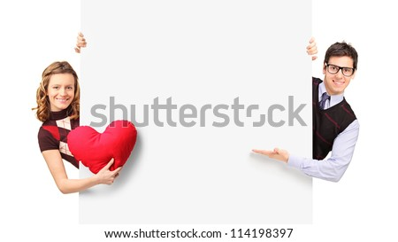 Young couple peeking out of a banner isolated on white background - stock photo