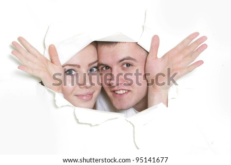 young couple peeping through hole in paper - stock photo