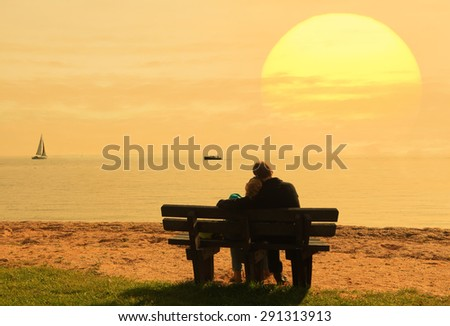 Young couple ( people silhouettes) sitting on a bench against a seaside sunset - stock photo