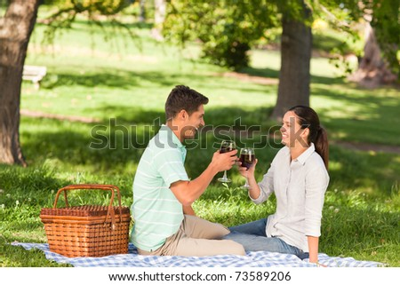 Young couple picnicking in the park - stock photo