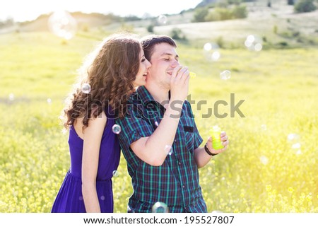 Young couple play together with bubble blower - stock photo
