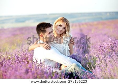 Young couple playing around in the lavender fields. Soft focus - stock photo