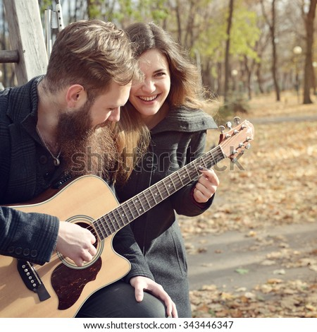 Young couple playing guitar together in autumn park outdoor, image toned and noise added. Hipster man with beard and moustache with his beautiful happy smiling girlfriend have fun outside. - stock photo
