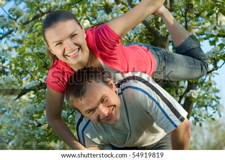 Young couple playing in a flowering garden and looking at the camera - stock photo