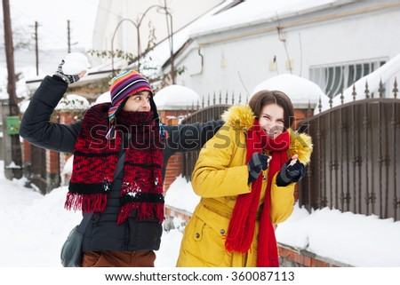 young couple playing snowballsnear the house - stock photo