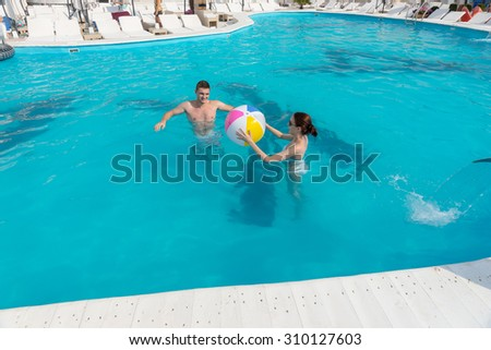 Young couple playing together in a resort swimming pool throwing a colorful beach ball to each other - stock photo