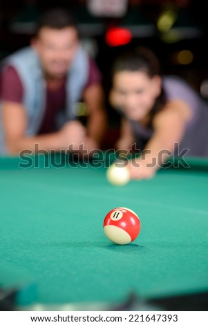 Young couple plays billiards in the dark billiard club - stock photo