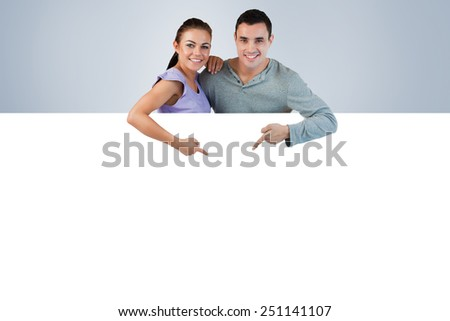 Young couple pointing at advertisement below them against grey vignette - stock photo