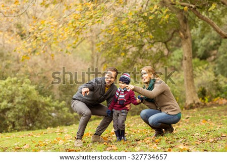 Young couple pointing something to their little boy on an autumns day - stock photo
