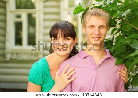 Young couple pose near wooden village house, wife hug husband - stock photo