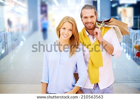 Young couple posing in shopping mall - stock photo