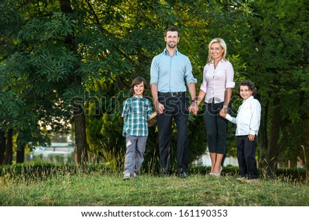 Young couple posing in the park with two kids - stock photo