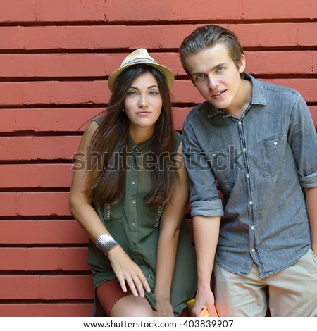 Young couple posing summer outdoor against red brick wall. Urban lifestyle, happiness, joy, friends, teenage, first love concept. Image toned and noise added. - stock photo