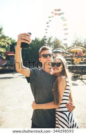 Young couple posing together at an attractions park arcade and using their smartphone to take a picture of themselves - stock photo