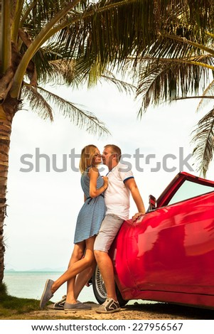 Young couple posing with a red and nostalgic car on tropical beach. - stock photo