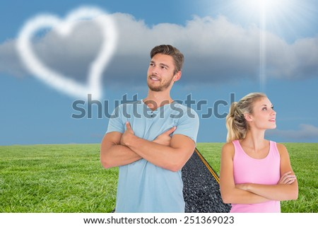 Young couple posing with arms crossed against road on grass - stock photo