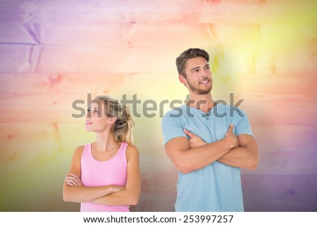Young couple posing with arms crossed against yellow and purple planks - stock photo