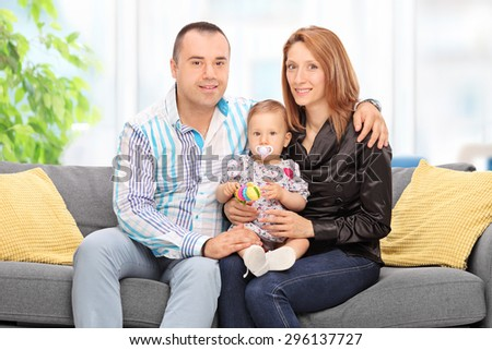 Young couple posing with their baby daughter seated on a gray couch at home - stock photo