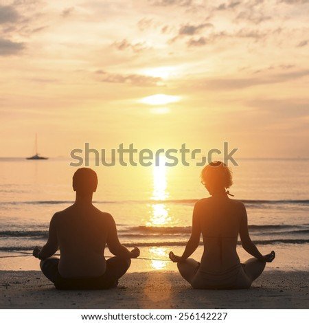Young couple practicing yoga on Sea beach during sunset.  - stock photo