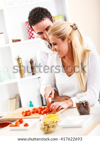 Young couple prepare vegetable salad for lunch.They are standing by the kitchen table. - stock photo